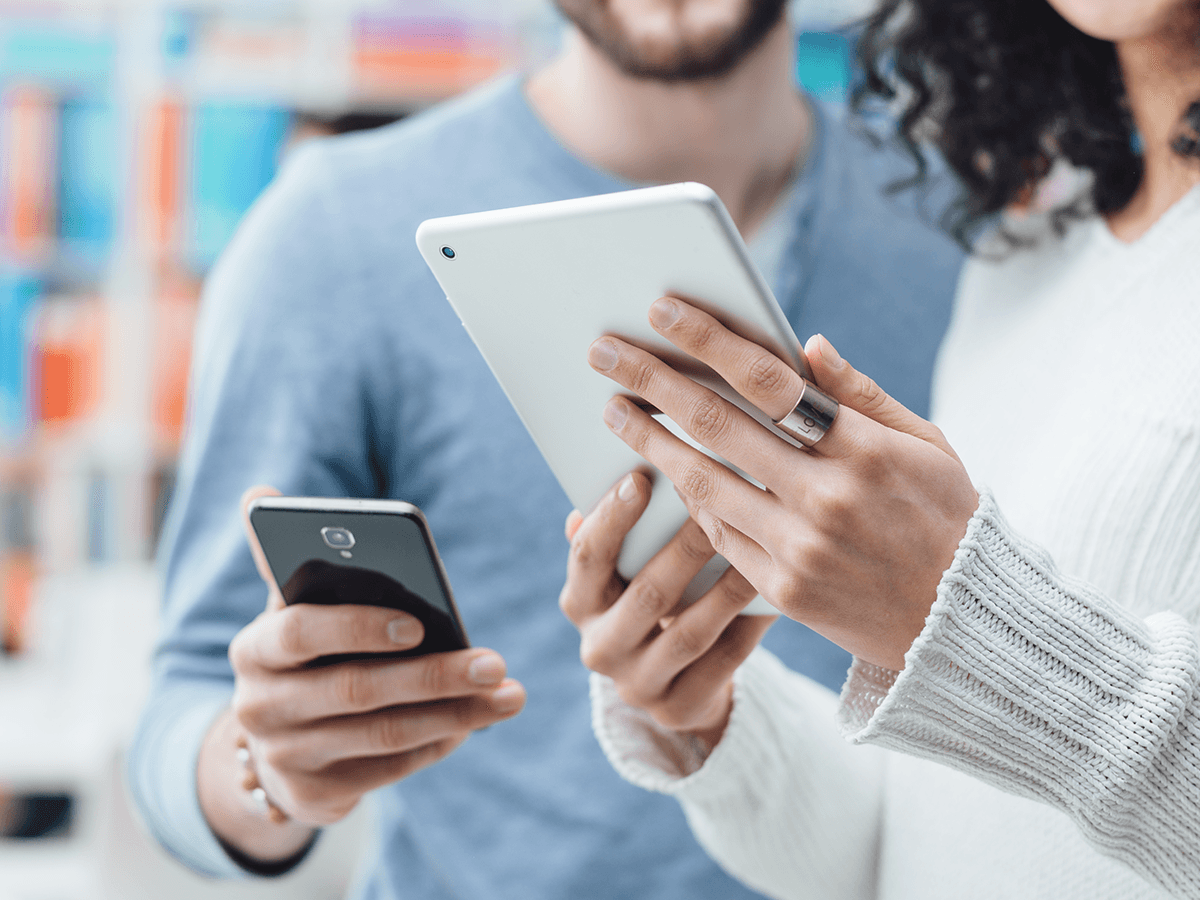 Technology consultants exchanging information on mobile devices
